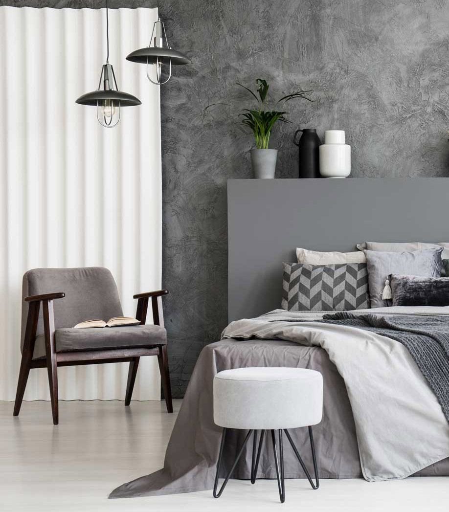 Grey armchair and stool near bed with headboard in bedroom inter
